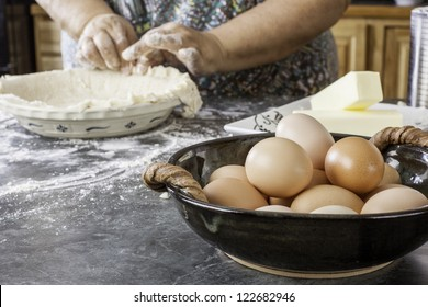 Interesting composition of baking ingredients with a old woman's hands preparing a pie crust out of focus in the background