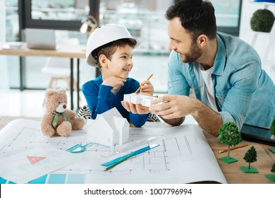 Interesting discoveries. Cheerful little boy in a hard hat and his loving father sitting in the office and examining the models of constructions