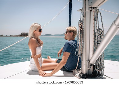 Interesting fascinated blonde couple, a man and a woman sitting and discussing something, taken away by conversation, posing on a white expensive yacht and looking at each other. emotions concept