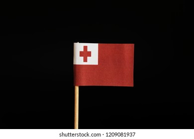 A interesting flag of Tonga on wooden stick on black background. Tonga belongs to oceania