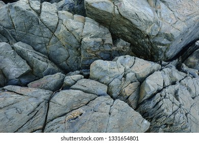 Interesting geometric patterns in coastal granite cliffs.