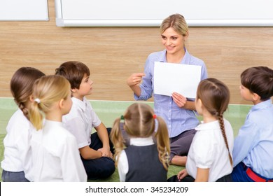 Interesting lesson. Young female teacher successfully communicating with her pupils by discussing a picture.