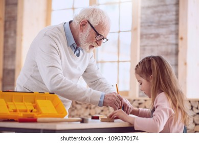 Interesting occupation. Smart nice man doing a drawing while helping his granddaughter