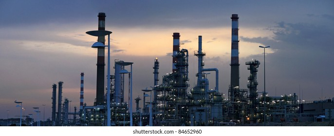 Interesting panorama of an oil refinery near a road  in the early morning light (dawn)