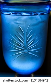 An interesting pattern on a blue chalice filled with ice water and condensation forming on the outside.