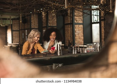 Interesting posts. Pleasant young women sitting at the bar counter and looking through social media timeline together while chuckling