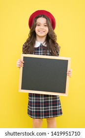 Interesting school lesson. Little child holding blank blackboard for private lesson on yellow background. Cute pupil having lesson at school. Small girl reciting a lesson at chalkboard, copy space.