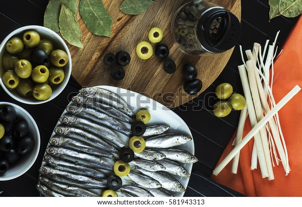 Interesting serving on the table of useful, tasty little fish sprat, condiments, olives and decor. The view from the top