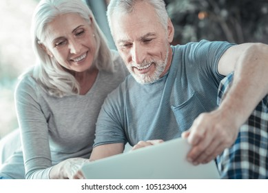 Interesting story. Pleasant senior lovely couple spending time together at home smiling and reading.