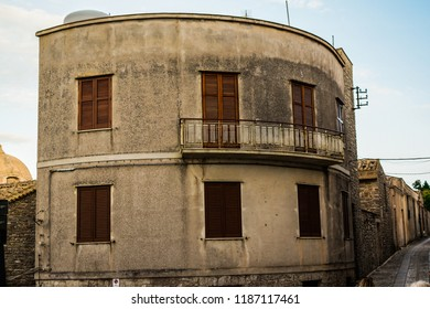 Interesting, strange, rounded house building in Erice, Sicily, Italy. Weird type of architecture, with the balcony on the 1st floor.  In the background narrow, Italian city street. Ancient style.