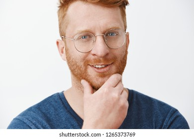 Interesting, I think you fit our company. Pleased intrigued creative and handsome redhead boss in blue t-shirt and glasses, touching beard, smiling from satisfied feelings, looking curiously at camera