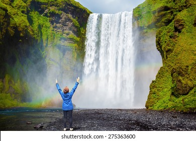 Interesting waterfall in Iceland - Skogafoss. Picturesque huge rainbow appears in the water mist. Middle-aged woman - tourist shocked beauty waterfall