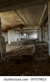 Interior of an abandoned administrative building. Interior ruins of an industrial factory. An old concrete staircase, ruins, corridor with garbage and mud, ruined walls of an unfinished office center