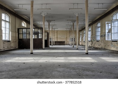 The interior of an abandoned hall with metal pillars