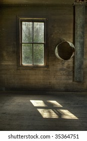 The interior of an abandoned vintage house with  natural light on floor from single window.