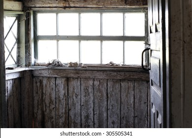 Interior of an abandoned wooden house, with light coming through the window.