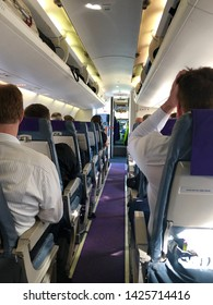 Interior of airplane with passengers on seats waiting for take off with door to the cockpit still open