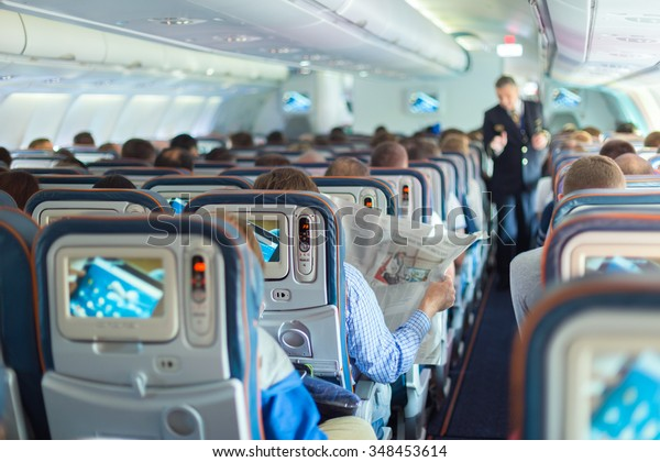 Interior of airplane with passengers on seats during flight. Steward in dark blue uniform walking the aisle. Horizontal composition.