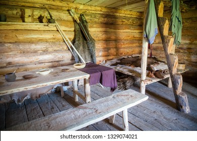 the interior of ancient peasant log cabin - a table and a bed