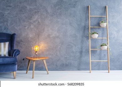 Interior with armchair, copper lamp, side table and flower stand