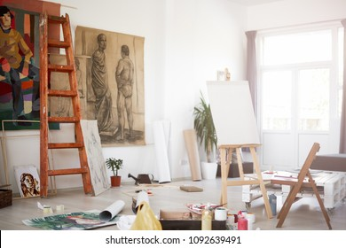 Interior of artist`s atelier. Paintings and painting material all around.