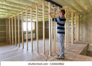 Interior of attic insulated room with oak floor under reconstruction. Young professional worker uses level and screwdriver installing wooden frame for future walls. Renovation and improvement concept.