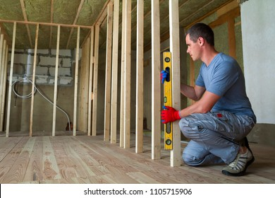 Interior of attic room with insulated ceiling and oak floor under reconstruction. Young professional worker uses level installing wooden frame for future walls. Renovation and improvement concept.