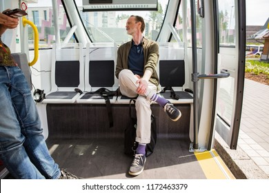 Interior of automated remotely operated bus in Helsinki. Unmanned public transport test on street. Passenger sitting on seat, waiting on bus stop.