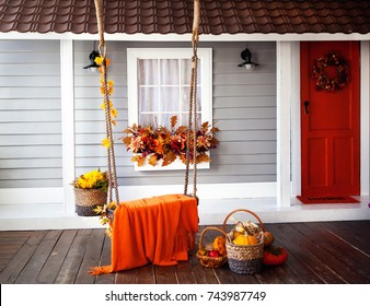 interior of an autumn patio. swing is adorned with autumn leaves and orange knitted plaid. Basket with pumpkins and autumn vegetables. The window is decorated with autumn decor. Bord door.
