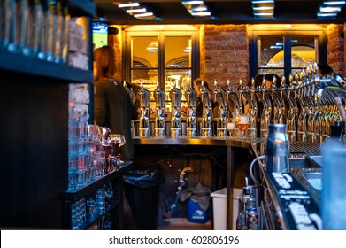 Interior of a bar counter with lots of beer taps for diverse type of beer being served: ale, lager, pilsner, stout, pale ale, wheat beer, porter, bock, mild ale, dunkel