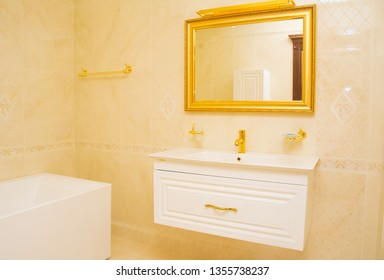 Interior of bathroom with gold faucet and mirror. Modern design of bathroom