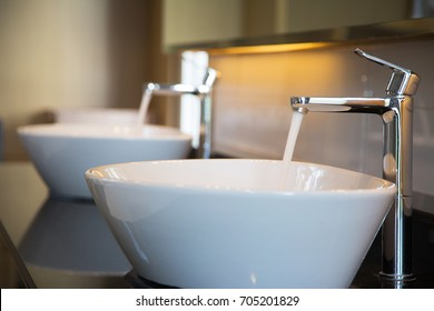 Interior of bathroom with sink basin faucet. Open chrome faucet washbasin. Modern design of bathroom
