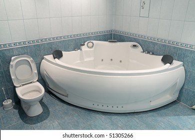 Interior of a bathroom with a toilet bowl and a jacuzzi