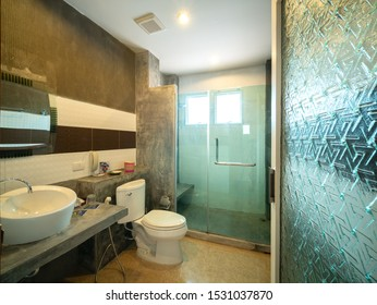 Interior of bathroom with toilet in warm light of f room of resort hotel, Thailand