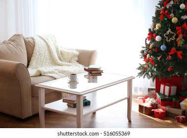 Interior of beautiful living room with table, sofa and Christmas tree