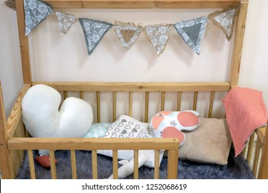 Interior of beautiful vintage children's room with crib and shelfs with toys.