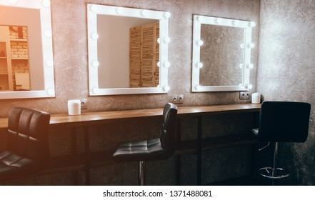 Interior of a beauty saloon. Room with makeup mirror lights and black chair