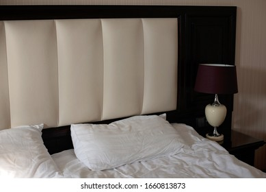 The interior of the bedroom in a classic style. Bed with nightstand and floor lamp. Hotel room.