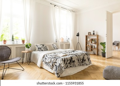 An interior of a bedroom with herringbone parquet, white walls and simple furniture. Bed, chair, bookcase, lamp, stool and pouf inside. Real photo.