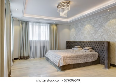 Interior of big empty bedroom with crystal chandelier in center of ceiling and big panoramic windows. Comfortable and cozy gray bed with big headboard. White wall with print of wallpapers.