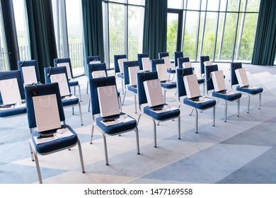 interior of big modern conference room with gifts and headphones on chairs for participants before starting a business seminar