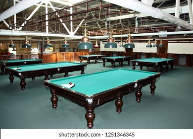 The interior of the billiard room, with green tables and lamps above them. On the tables are balls.