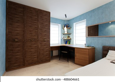 Interior of a boy's room with a big cabinet, a writing desk, a bed, a mirror and  blue wallpaper