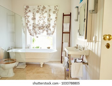 Interior of a bright country style bathroom with a basin, toilet and claw foot bathtub in a residential home