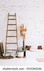 Interior of bright living room with white brick walls and couch bench with pillows. Dried high plants and wooden ladder near wall.
