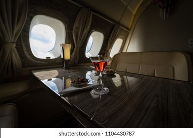 Interior of a business class of a commercial passenger plane, an armchair and a window, a table and a cocktail glass with a drink and almonds. Focus on a glass.