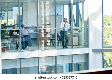 Interior of busy open plan office: creative designers brainstorming on joint project, middle-aged entrepreneur conducting telephone negotiations with business partner, view through panoramic windows
