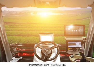 Interior cabin of smart agricultural tractor a combine and harvesting in farm field.