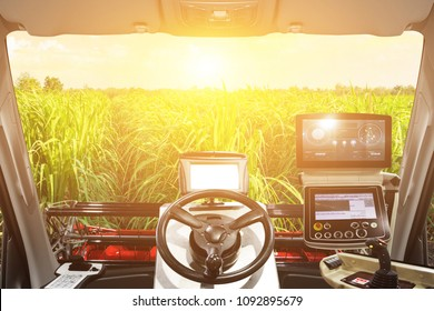 Interior cabin of smart agricultural tractor a combine and harvesting in sunrise.