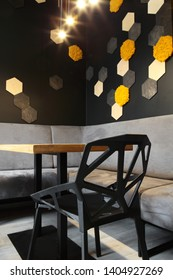 Interior of cafe . Loft space design, wooden table, concrete wall. creative minimalistic cafe interior, simplicity and geometry concept, black and yellow colors.Creative space.